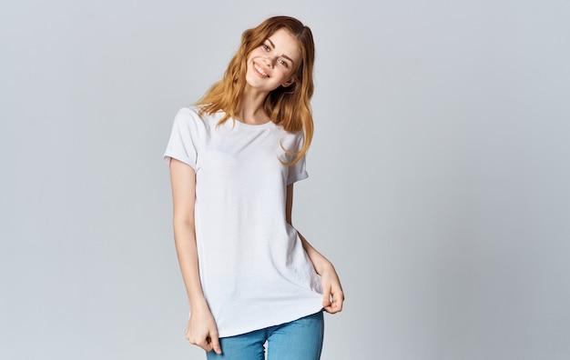Uma linda mulher em uma camiseta branca e jeans sorri em um fundo cinza e gesticula com as mãos.