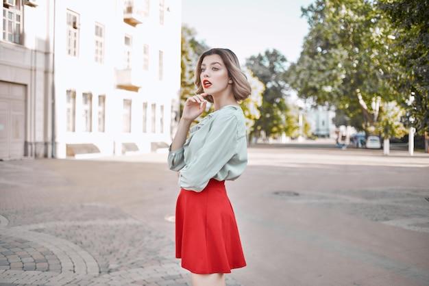 Uma linda mulher em uma cidade de saia vermelha, passeio divertido, estilo de vida, lazer