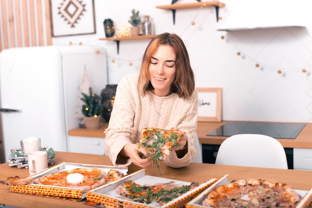 Uma linda mulher está escolhendo pizza com rúcula em casa na cozinha dela.