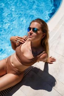 Uma linda mulher está sentada sozinha à beira da piscina. ela tem cabelo comprido e um maiô bege. ela é meiga e sexy em um biquíni relaxando na piscina