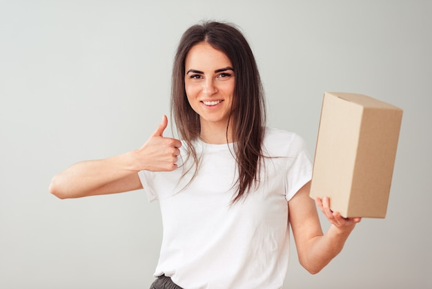 Uma linda mulher européia com um lindo sorriso segura uma caixa com um lugar vazio para um logotipo e mostra o polegar para cima da classe