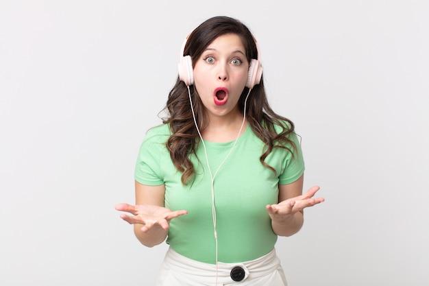 Uma linda mulher extremamente chocada e surpresa ouvindo música com fones de ouvido