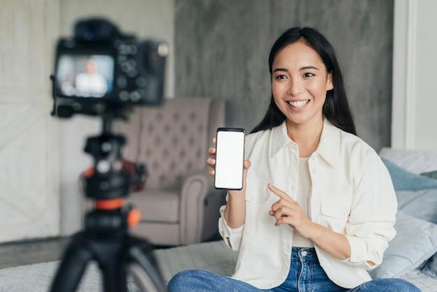 Uma linda mulher fazendo vlogs e apontando para o telefone