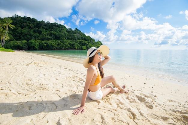 Uma linda mulher feliz de biquíni amarelo curtindo e relaxando na praia, conceito de verão e férias