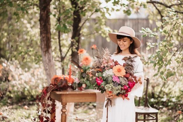 Uma linda mulher feliz segura um buquê de flores e ervas nas mãos