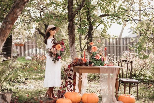 Uma linda mulher feliz tem um buquê de flores e ervas nas mãos. clima de outono