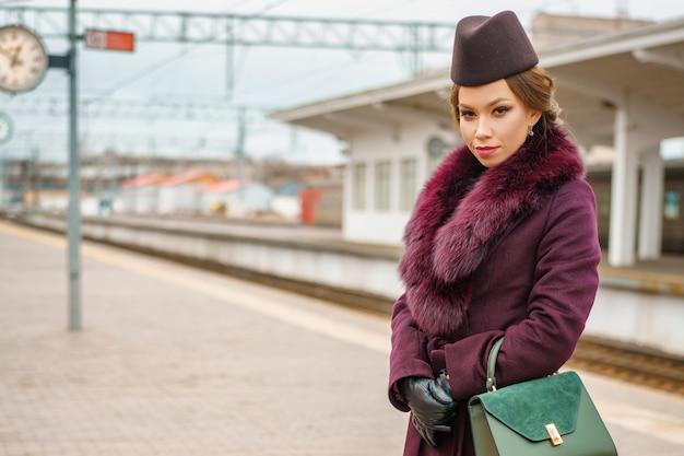 Uma linda mulher glamourosa fica na plataforma da estação ferroviária com um casaco.