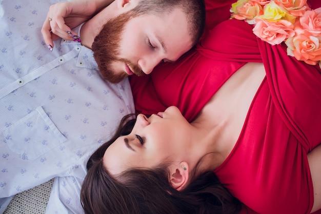 Uma linda mulher grávida em lingerie preta encontra-se em um véu cinza. a cama está decorada com flores frescas. a menina tem cabelo loiro, ela sorri. vista de cima.