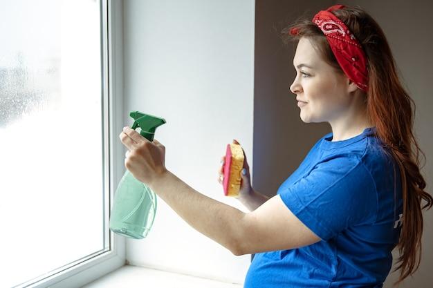 Uma linda mulher grávida nos últimos meses de gravidez se dedica à limpeza e lava as janelas.