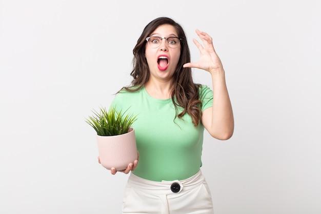 Uma linda mulher gritando com as mãos para o alto e segurando uma planta decorativa