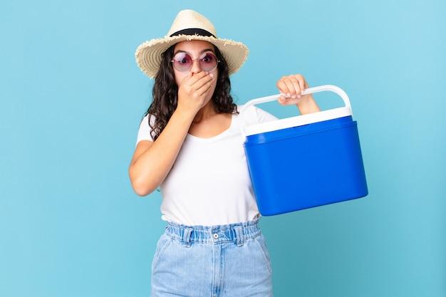 Uma linda mulher hispânica cobrindo a boca com as mãos com um choque segurando uma geladeira portátil