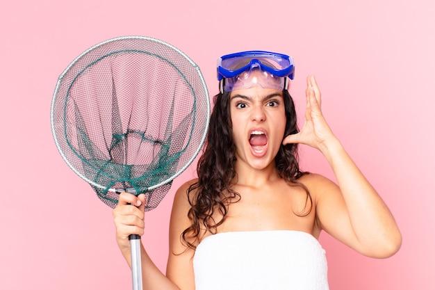 Uma linda mulher hispânica gritando com as mãos no ar com óculos de proteção e rede de pesca