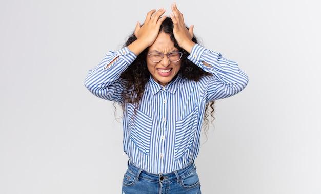 Uma linda mulher hispânica se sentindo estressada e ansiosa, deprimida e frustrada com uma dor de cabeça, levando as duas mãos à cabeça