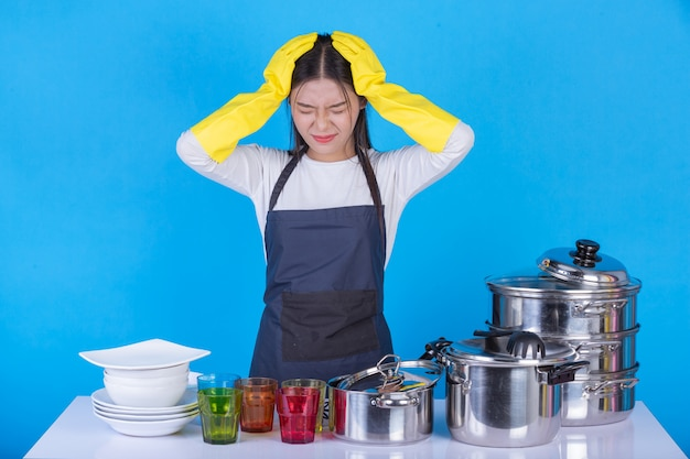 Uma linda mulher lavando pratos na frente dele em um azul.
