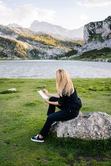 Uma linda mulher loira caucasiana escreve e desenha em um bloco de notas em uma paisagem de montanha com lago