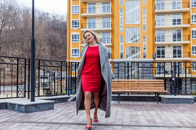 Uma linda mulher loira com um casaco cinza com um padrão de bordado. a mulher está posando na varanda com uma cerca decorativa em meio urbano.