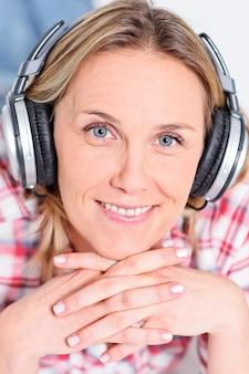 Uma linda mulher loira ouvindo música com fones de ouvido