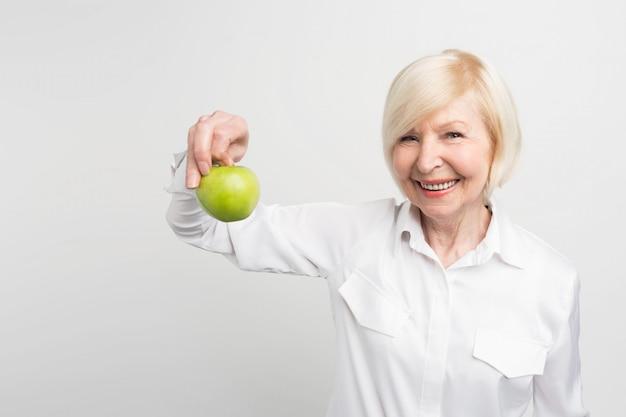 Uma linda mulher madura, segurando uma maçã verde na mão direita. ela gosta de comer frutas. essa é a escolha dela.
