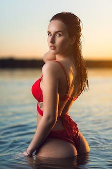 Uma linda mulher morena em um maiô vermelho está descansando na praia à beira-mar. menina bonita magrinha em praia tropical