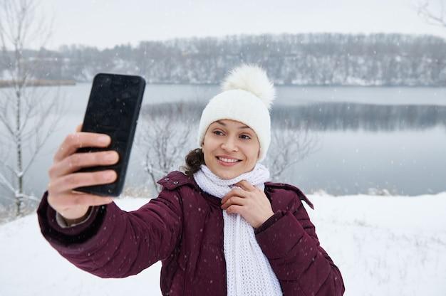 Uma linda mulher morena fazendo uma selfie no fundo de uma paisagem coberta de neve enquanto cai neve