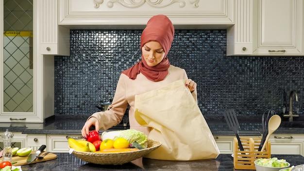 Uma linda mulher muçulmana usando hijab tira produtos comprados de uma sacola grande para fazer o jantar na cozinha.
