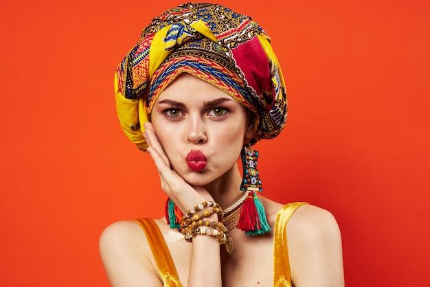 Uma linda mulher multicolorida turbante decoração lábios vermelhos atraente olhar parede vermelha.