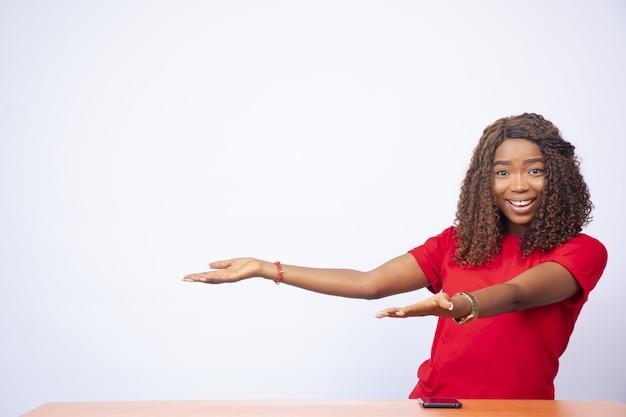 Uma linda mulher negra gesticula para o espaço vazio ao seu lado, na frente de um branco