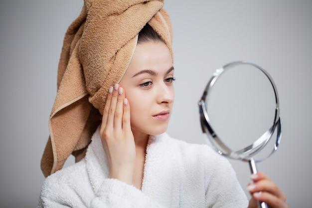 Uma linda mulher olha no espelho depois do banho