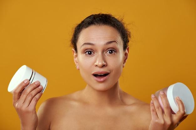 Uma linda mulher parece surpresa com a câmera enquanto segura potes de cremes isolados em um fundo amarelo
