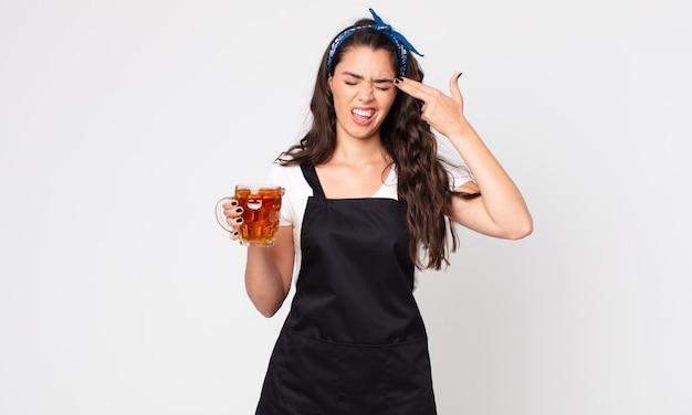 Uma linda mulher parecendo infeliz e estressada, gesto suicida fazendo sinal de arma e segurando um copo de cerveja