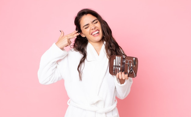 Uma linda mulher parecendo infeliz e estressada, gesto suicida fazendo sinal de arma e segurando uma bolsa de maquiagem com ferramentas de unhas