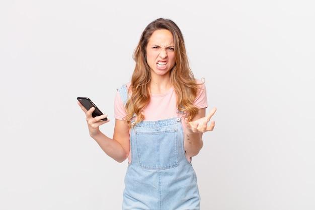 Uma linda mulher parecendo zangada, irritada e frustrada segurando um smartphone