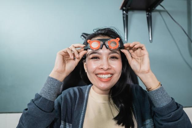Uma linda mulher posa segurando óculos de medição que estão sendo usados em uma sala de uma clínica de olhos