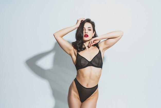 Uma linda mulher posando de lingerie em um fundo branco