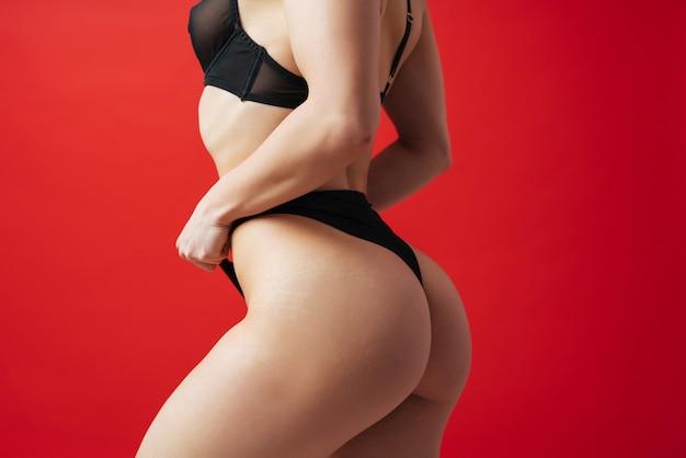 Uma linda mulher posando de lingerie em um fundo de cor vermelha