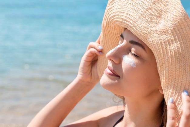 Uma linda mulher protege a pele do rosto com protetor solar na praia.