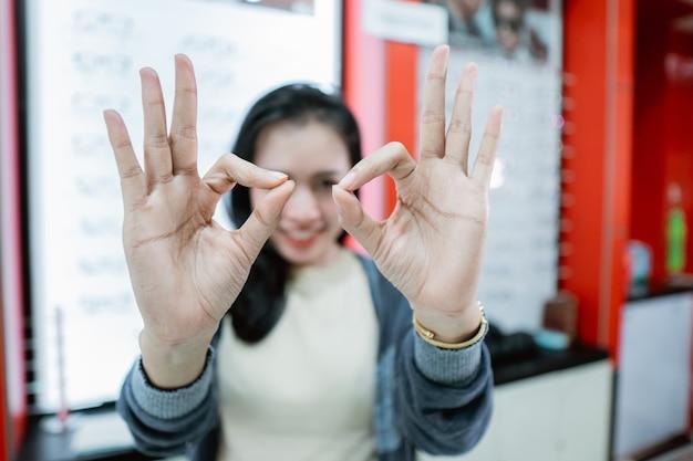 Uma linda mulher que sorri está em uma clínica de olhos e forma um emblema de óculos usando a mão na frente do fundo da janela de exibição de óculos