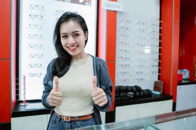 Uma linda mulher que sorri está em uma clínica oftalmológica dando uma recomendação com um plano de fundo de uma vitrine de óculos