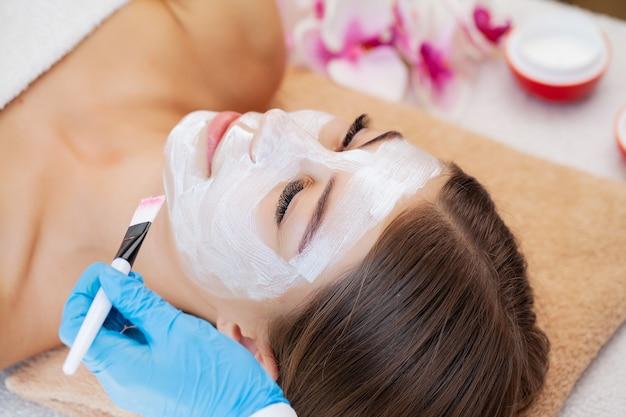 Uma linda mulher relaxa durante os tratamentos de spa no salão de beleza.