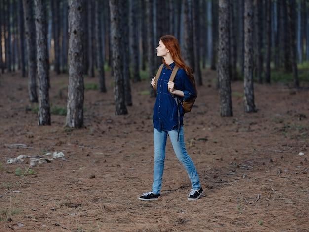 Uma linda mulher ruiva com mochila de alpinista, viagem pela floresta