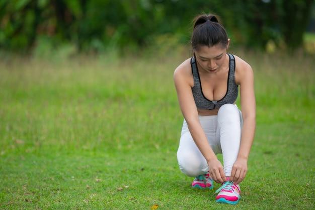 Uma linda mulher se preparando para exercitar no parque.