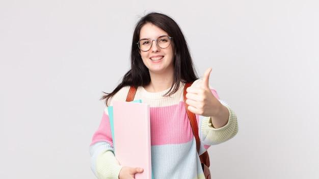 Uma linda mulher se sentindo orgulhosa, sorrindo positivamente com o polegar para cima. conceito de estudante universitário