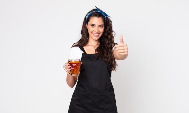 Uma linda mulher se sentindo orgulhosa, sorrindo positivamente com o polegar para cima e segurando um copo de cerveja Foto Premium
