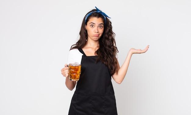 Uma linda mulher se sentindo perplexa e confusa, duvidando e segurando um copo de cerveja