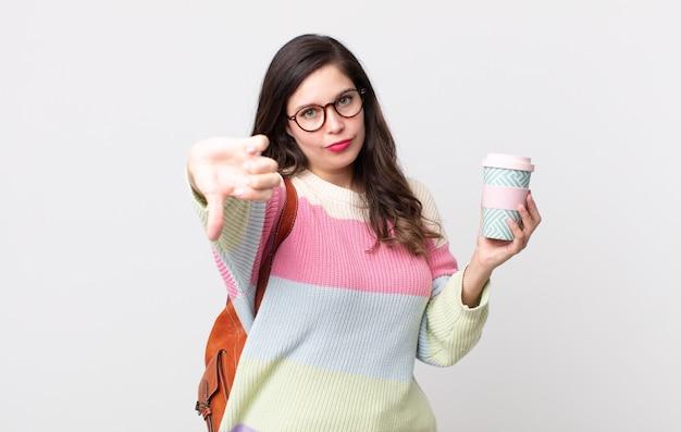 Uma linda mulher se sentindo zangada, mostrando os polegares para baixo. conceito de estudante