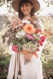 Uma linda mulher segura um buquê de flores e ervas nas mãos