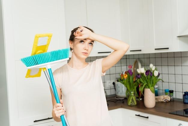 Uma linda mulher segura uma esfregona e escova para limpar nas mãos e suspira de fadiga