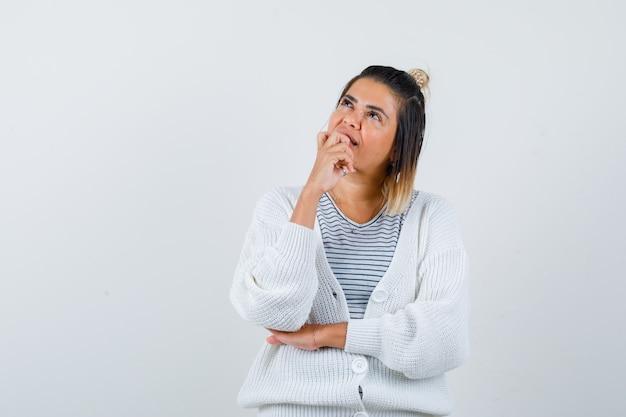 Uma linda mulher segurando a mão no queixo, olhando para cima com uma camiseta, um cardigã e parecendo pensativa
