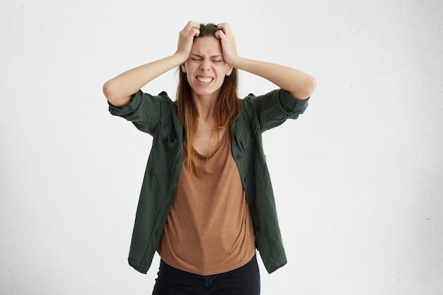 Uma linda mulher segurando as mãos na cabeça, tendo decepção e situação estressante, parecendo frustrada e cheia de tristeza, fechando os olhos enquanto chora