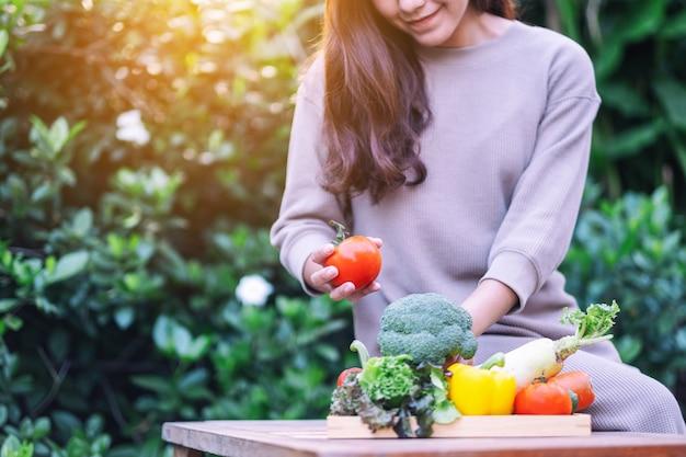 Uma linda mulher segurando e colhendo vegetais frescos de uma bandeja de madeira sobre a mesa